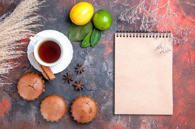 Cake cupcakes a cup of tea with cinnamon sticks wheat ears notebook star anise