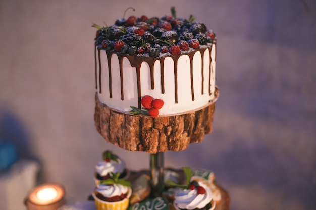 Cake and cupcakes with berries on a wooden shelf in candle light