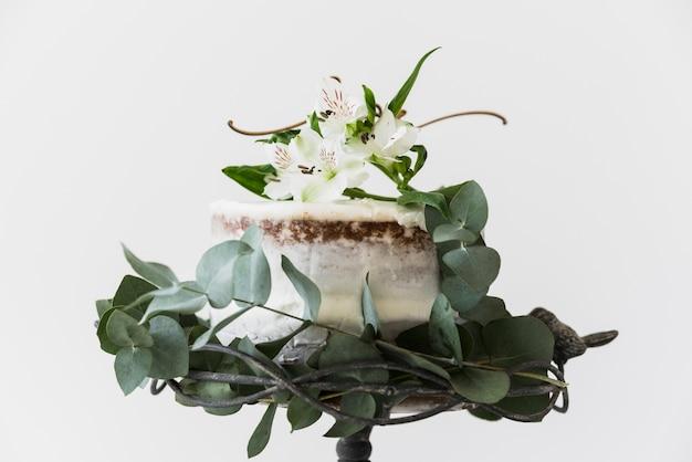 Торт украшен цветами альстромерии и зелеными листьями на белом фоне