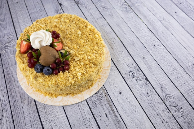 Cake decorated with berries close-up on a white wooden table
