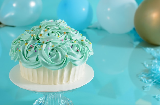 Cake decorated with blue flowers on a photo studio background