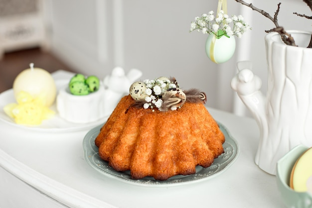 Cake decorated with eggs and feathers on a plate