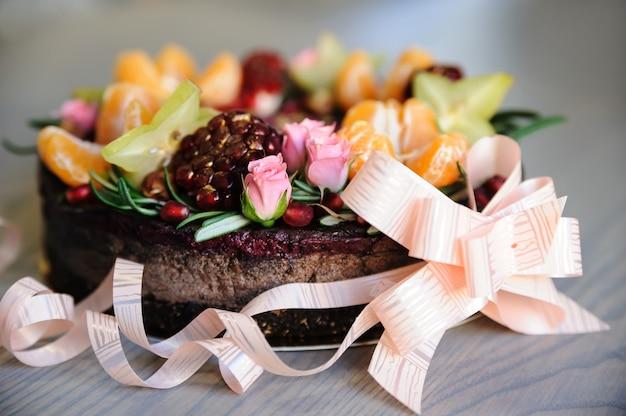 Торт украшен свежими фруктами, цветами и лесными орехами.