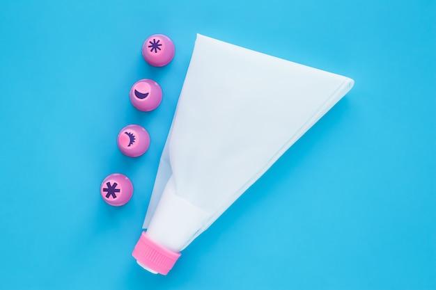 케이크 꾸미기 도구. 장식 빵 굽기를위한 백색 생과자 부대 및 분홍색 플라스틱 분사구.