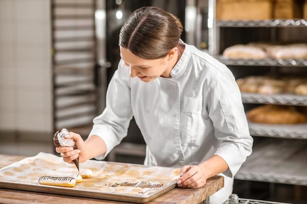 케이크, 에클 레어. 기성품 eclairs의 표면을 장식하는 베이킹 시트 위에 생과자 가방을 들고 세심한 영감을 얻은 여성