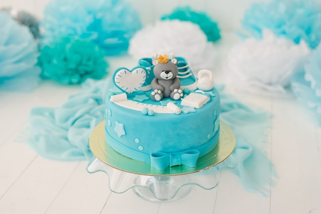 Cake for the first birthday of a boy with a bear in blue.