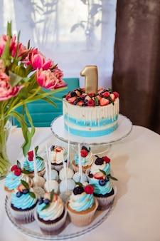 1 년 생일 파티 케이크, 캔디 바, 사탕 뷔페에 맛있는 과자, 신선한 딸기가 든 케이크, 어린이 생일. 첫 생일 케이크
