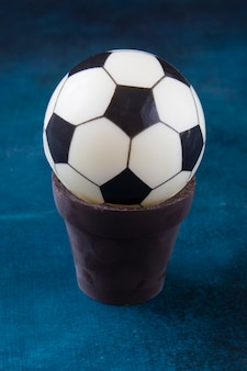 A cake in the form of a black and white ball in a chocolate pot on the table as a gift to a sweet tooth and a fan of european football