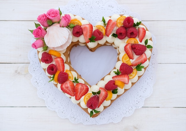 Cake in the form of a heart with cheese cream and berries