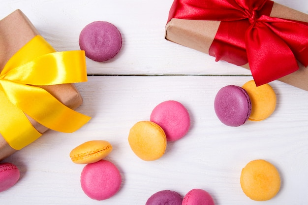 ケーキフランスマカロンイエロー、ピンク、パープルカラーホワイトヴィンテージ木とギフトリボン表面トップビュー