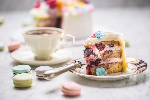マジパンの花のマカロンとブラックコーヒーのカップからのケーキ。