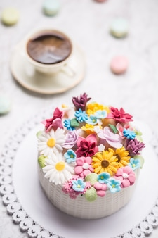 Cake from marzipan flowers macaroons and a cup of black coffee.