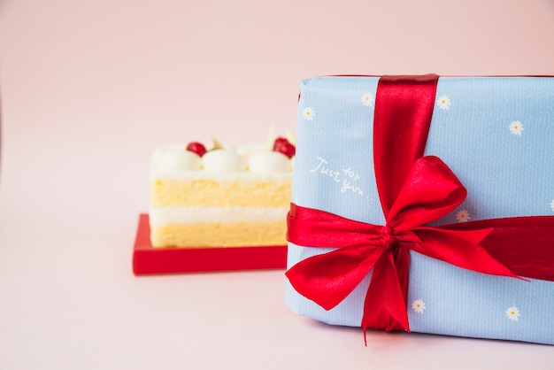 Cake and gift box wrapped with blue paper and red ribbon bow on pink background
