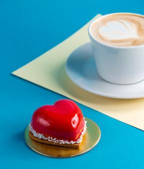一杯のコーヒーと青のケーキハート型のムースケーキ