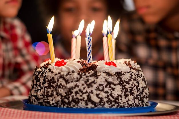 子供の前のケーキキャンドル付きの小さなバースデーケーキはこれを食べるのを待つことができませんそれは非常に特別な休日です