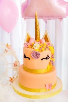 큰 황금 뿔이있는 유니콘 형태의 케이크
