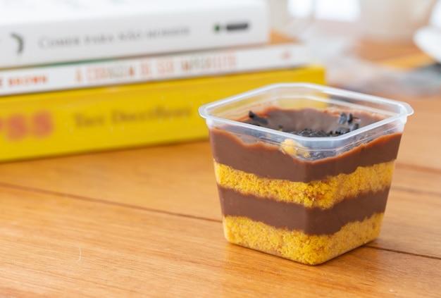 Торт в горшочке на деревянном столе и книгах на заднем плане.