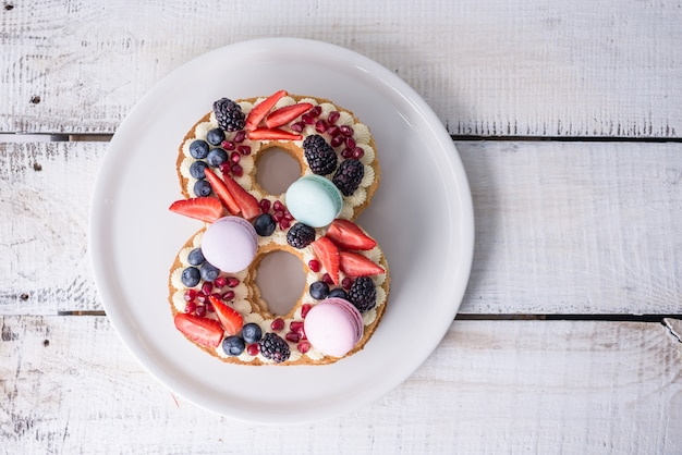 흰색 크림과 딸기로 장식 된 숫자 8 모양의 케이크