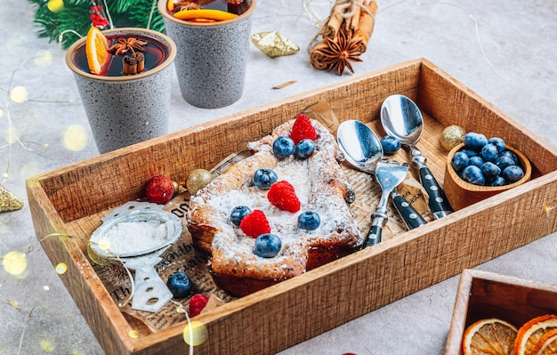 新聞と木製のトレイの形でベーキングペーパーにクリスマスツリーの形をしたケーキ。セレクティブフォーカス