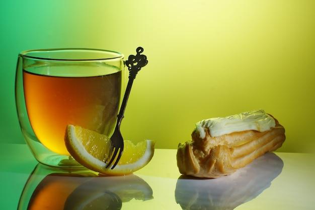 Торт, лимон и чай в прозрачном стакане на столе