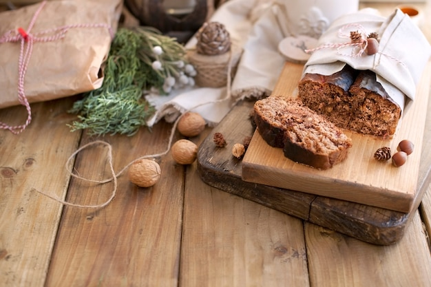 Cake loaf with nuts and chocolate on a wooden board
