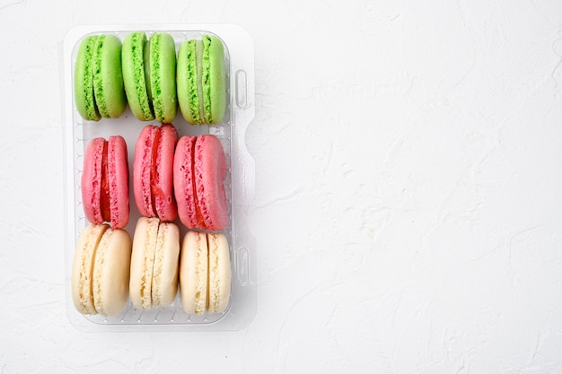 Cake macaron or macaroon set, in plastic pack, on white stone table background, top view flat lay, with copy space for text
