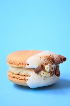 Торт макарон или миндальное печенье на синей стене. разноцветное миндальное печенье. французский макарун торт крупным планом