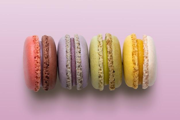 ピンクの背景の上面図にケーキマカロンまたはマカロン