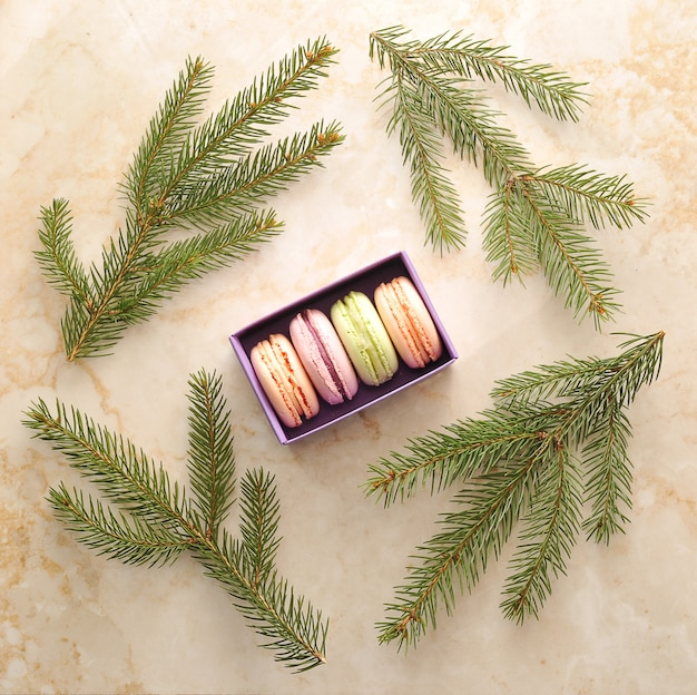 Cake macarons in a purple box with the branches of a christmas tree