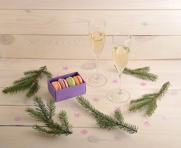 Cake macarons with champagne and branch of christmas tree