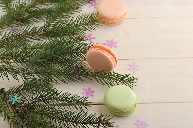 Cake macarons with christmas tree branches and snowflakes on wooden background