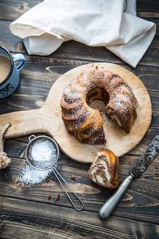 Торт. чашка мраморного торта кофейной пудры, сахара, кухонной посуды, винтажной посуды и ягод свежих фруктов.