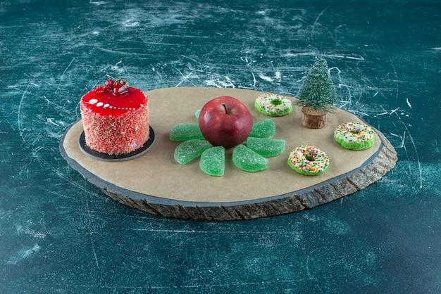 Torta, marmellate, ciambelle e una mela su una tavola sull'azzurro.