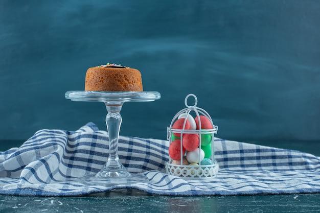 Торт на стеклянном постаменте рядом с шоколадом в клетке на полотенце, на синем фоне. фото высокого качества