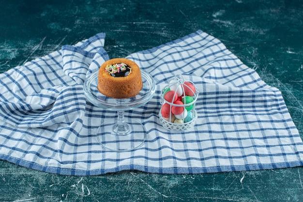 青い表面のタオルの上のケージのチョコレートの横にあるガラスの台座の上のケーキ