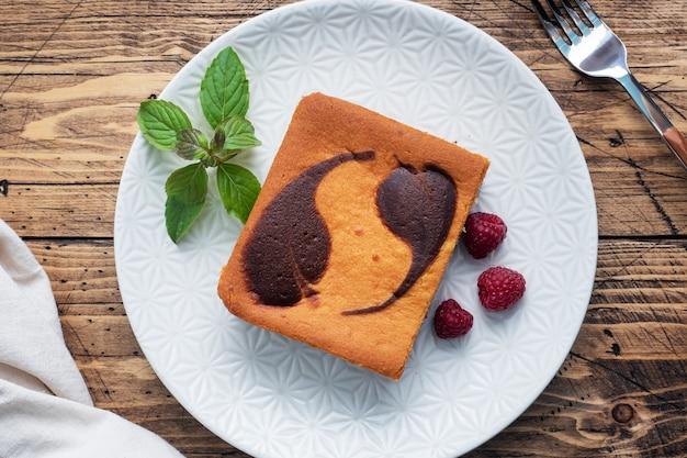 Торт на тарелке шоколадных пирожных и творожного чизкейка с малиной
