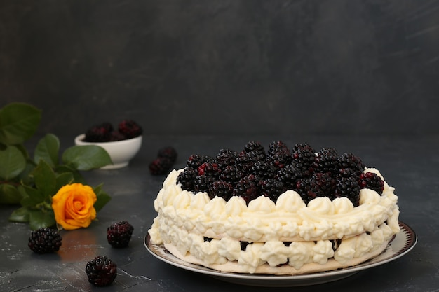 Cake pavlova with blackberries and whipped cream, located on a dark background
