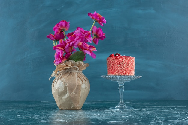 Cake on a pedestal next to a vase of flowers on blue.