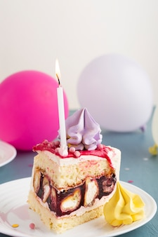 Кусок торта со свечой и воздушными шарами
