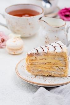 Cake on plate with tea and macarons