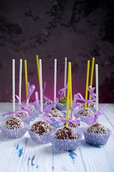 Cake pops coated chocolate with sprinkling on wooden table table on dark background with copy space