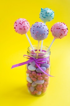 Cake pops in the glass jar on the yellow