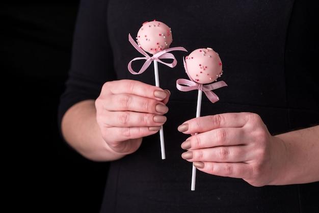 黒の背景に女性の手でケーキが飛び出します。ピンクチョコレートクリームのパウダーとリボンのデザート。