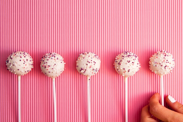 ケーキは手でピンクの表面に一列に棒でポップします。美味しくて美しいお菓子