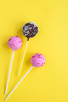 Cake pops with pink and chocolate glaze on the yellow background