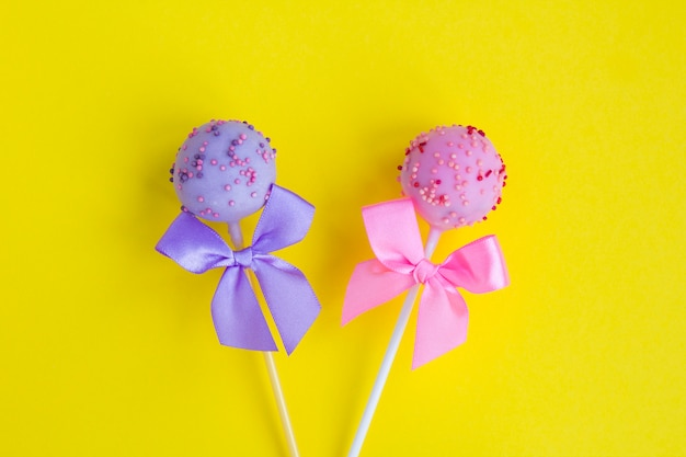 Cake pops with pink and violet bows on the yellow