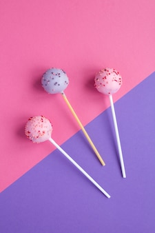 Cake pops with pink and violet glaze  on the two-color background. top view. copy space. location vertical.