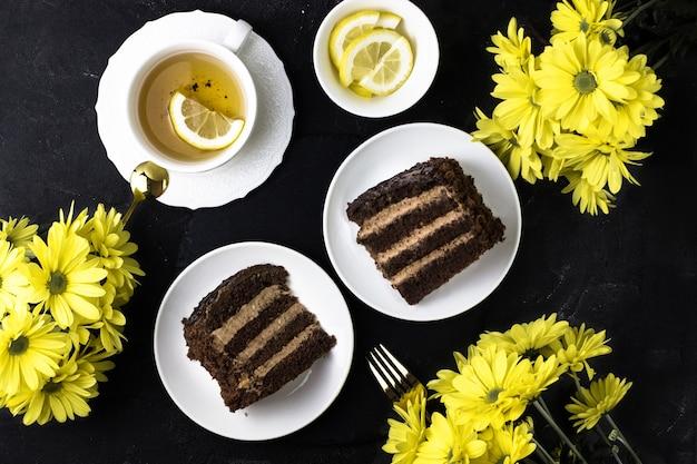 노란 국화에 대 한 검은 테이블에 케이크 프라하. 초콜릿 케이크와 레몬 차