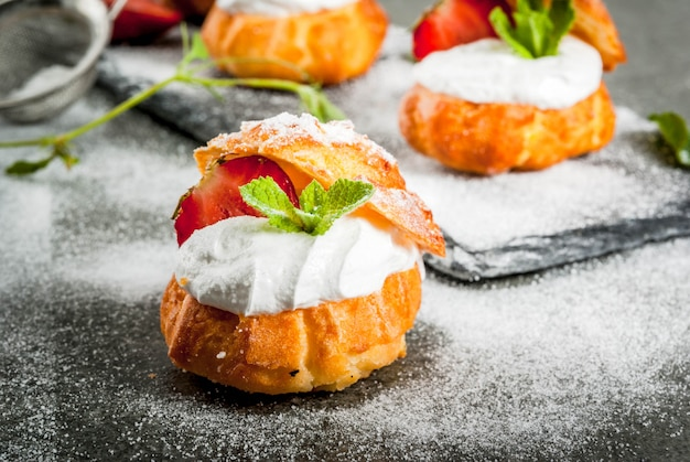 Cake profiteroles with whipped cream, fresh strawberries, mint and sprinkling of powdered sugar.