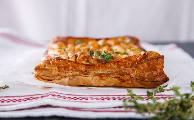 Cake of puff pastry with savory stuffing and thyme